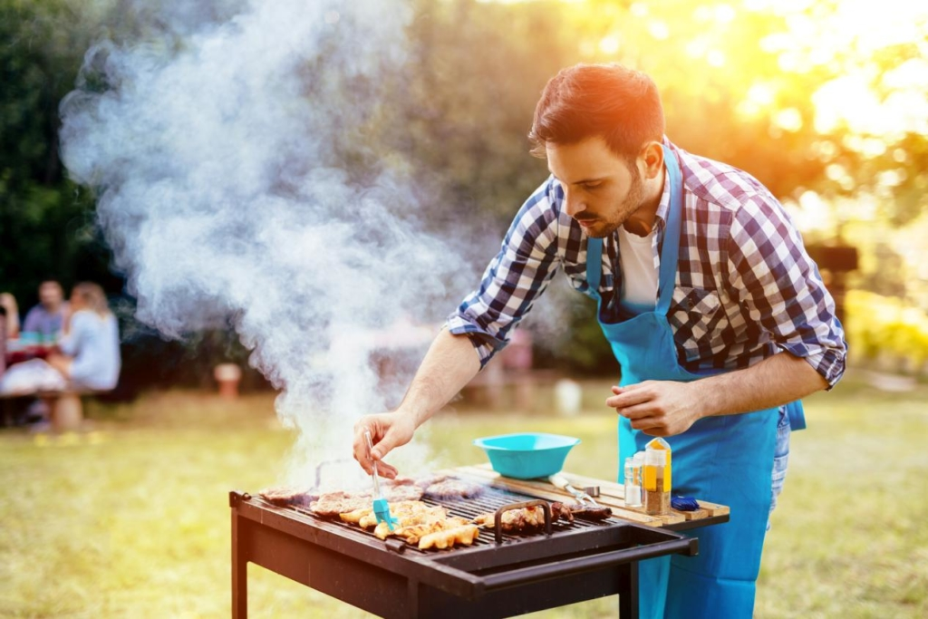 Handsome male preparing barbecue